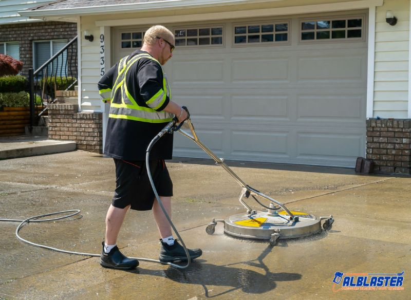 Technician is performing residential pressure washing on a driveway