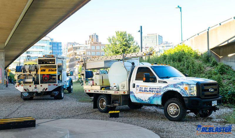 Alblaster pressure washing trucks are parked under Cambie Bridge before starting the job.