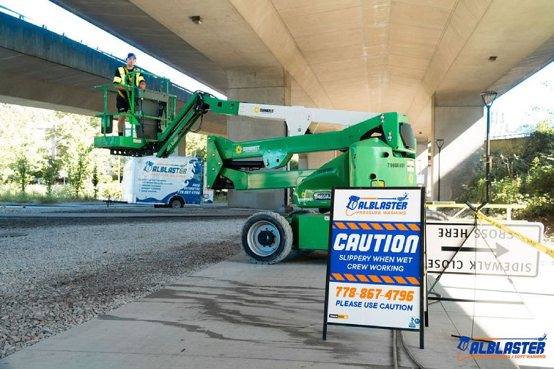 A pressure washing contractor is adjusting the ladder before start washing the bottom of the bridge.