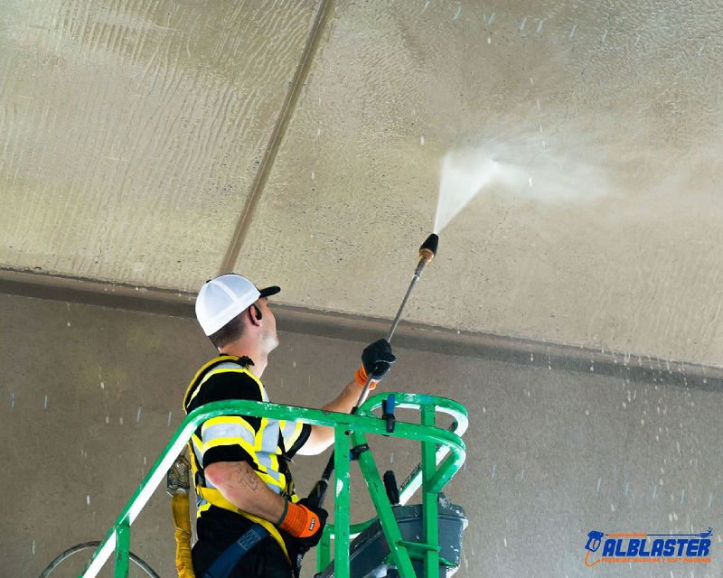 A contractor on a ladder is performing pressure washing on Cambie Bridge in Vancouver
