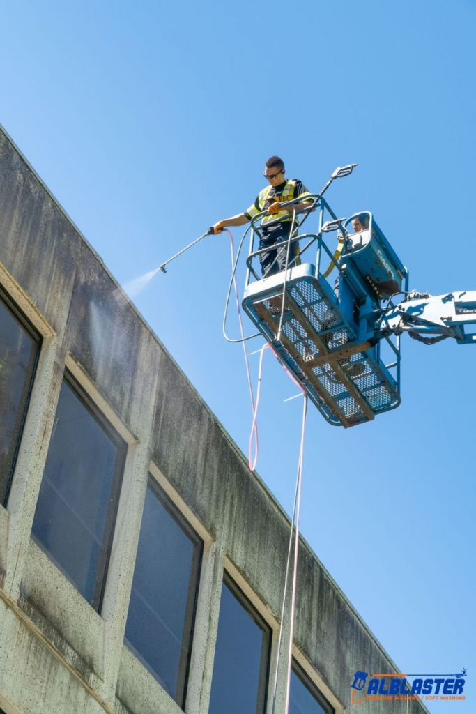 Soft washing from a ladder on a commercial building
