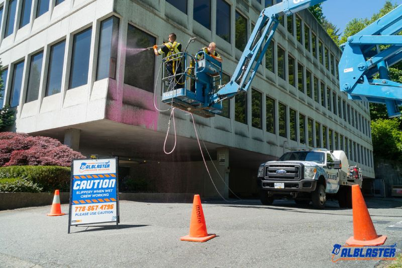 Soft washing from a ladder on a commercial building's facade