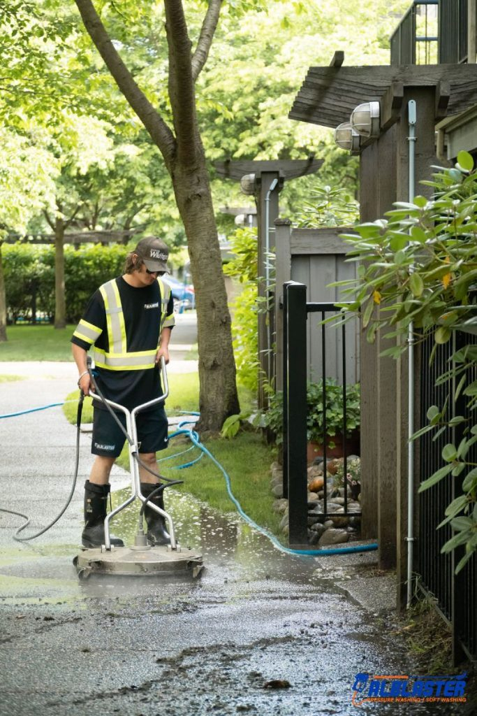 Our crew member cleaning a sidewalk with pressure washing