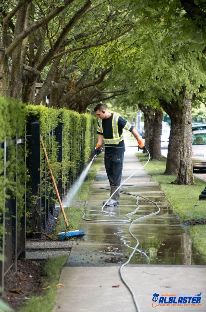 Crew member pressure washing a sidewalk